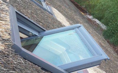 Une fenêtre de toit sur une toiture en chaume